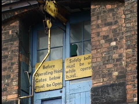 Warning signs on door of derelict industrial building in Derby