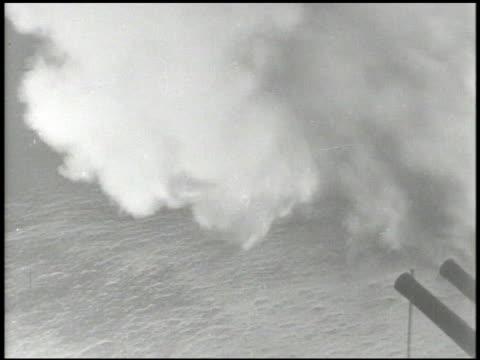 Warship firing guns VS Guns firing ammunition light briefly lighting area WS Ship explosion burning on fire MS BEHIND Person on deck in helmet using...