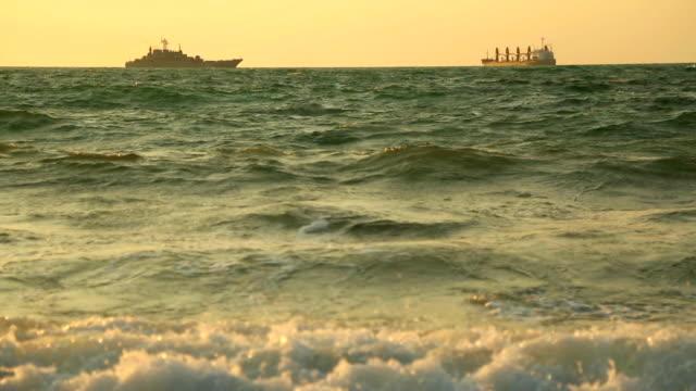 warship guarding cargo ships in the sea