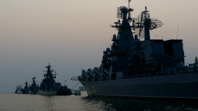 warships in the bay at anchor at sunset