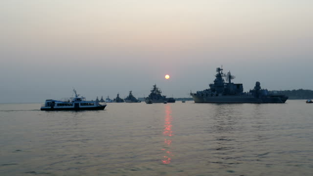 warships in the bay at sunset