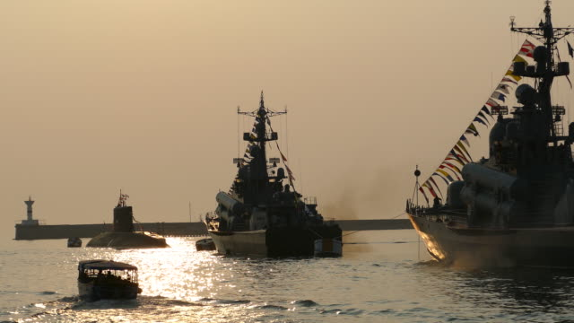 warships in the bay during a beautiful sunset