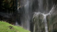 Water cascades over falls into alpine meadow