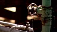 Water drips from a pipe and fixtures. Available in HD.