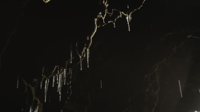 Water drips from icicles in a cave.