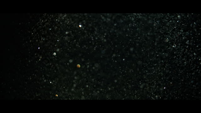Water drops or very heavy rain falling against black