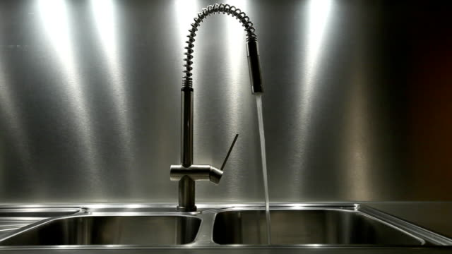 Water flowing out faucet into metal sink