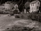 Water flows past damaged buildings in the village of Lynmouth following the flood disaster