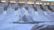 Water flows through frozen dam