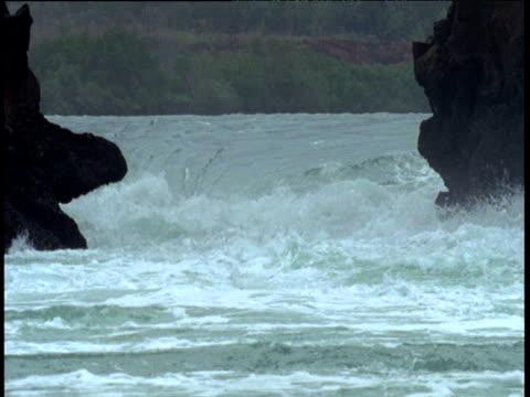 Water gushing through channel between two rocks, Talbot Bay, Australia