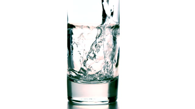Water pouring into a glass on white background