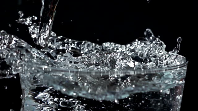 Filling a glass of water with splashes in slow motion