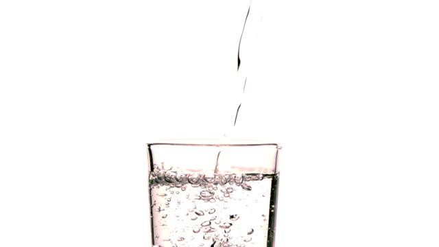 Acqua Versare in un bicchiere su sfondo bianco