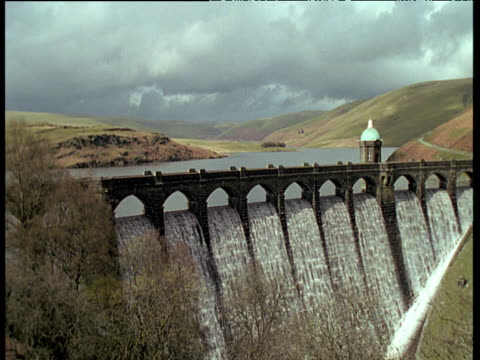 Water rushes down Elan Valley dam under cloudy sky, rolling hills in distance and trees in foreground, Wales