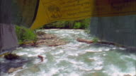 Water rushes over rocks in river framed by prayer flag, Paro Available in HD.