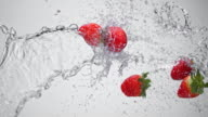 SLO MO Water splashing strawberries in the air