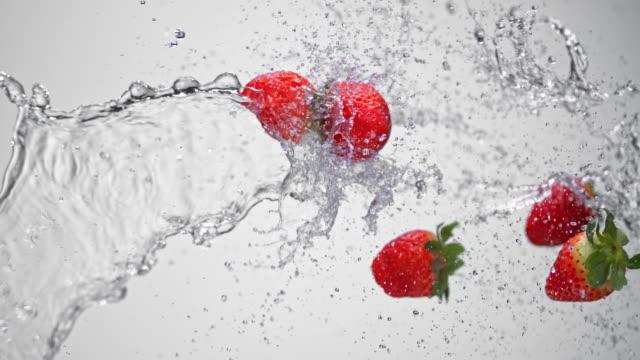 SLO MO Water splashing strawberries in the air