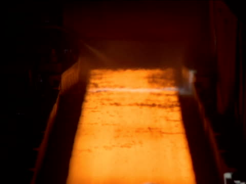 Water sprays on hot glowing metal sheet moving on conveyor, creating clouds of steam, South Africa