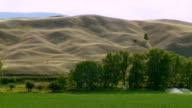 WS PAN Water sprinklers on grazing land with mountains in background / Near Williams Lake, British Columbia, Canada