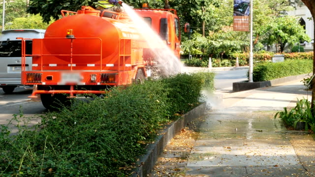 water tanker watering trees in the park