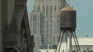 MS Water tower with Empire States building in background on hot summer day / New York City, New York, USA