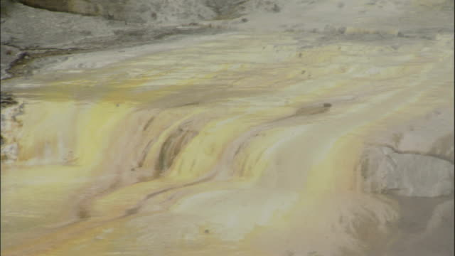 Water trickles over mineral deposits and into a geothermal pool. Available in HD.