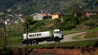 MS SLO MO water truck driving up hill in rural township/ KwaZulu-Natal/ South Africa