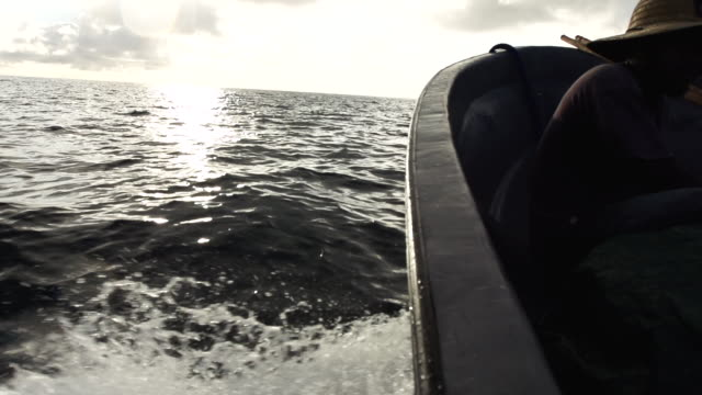 Water wake at sunrise as boat moves fast through choppy water, high speed