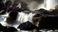 A waterfall crashes into a boulder-strewn pool. Available in HD.
