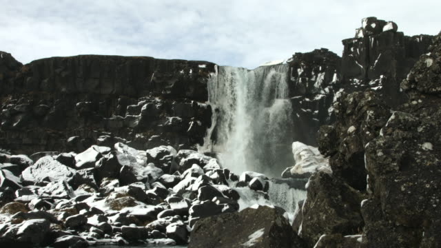 A waterfall flows over a cliff face at the Thingvellir National Park.