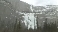 Waterfall frozen on steep craggy mountain side, Canadian Rocky Mountain Parks, Canada