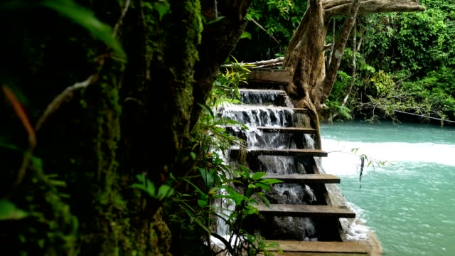 Waterfall of paradise with wood staircase slide shot