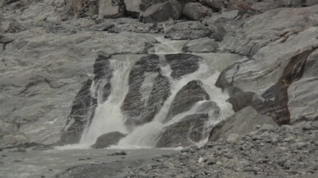 Waterfalls flowing with meltwater below face of Franz Josef Glacier in Westland Tai Poutini National Park