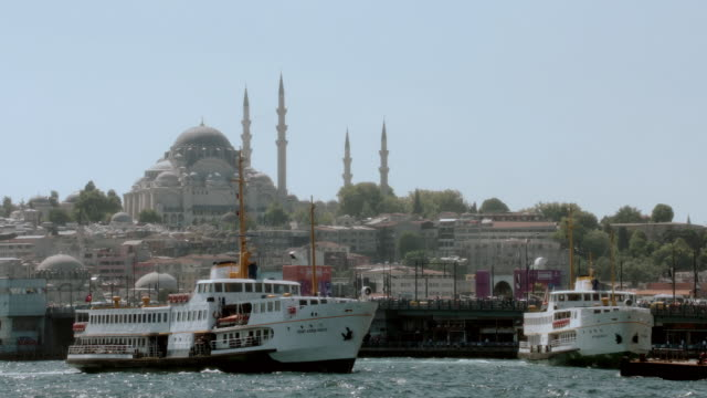 LA Waterfront properties and boats along the Bosphorus strait with the Hagia Sophia in the distance / Istanbul, Turkey