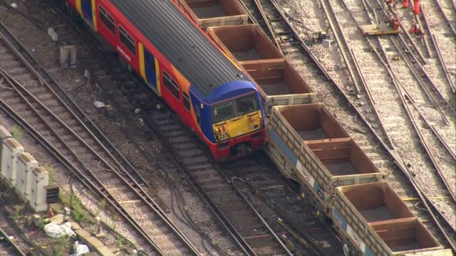 Aerial views ENGLAND London Battersea / Vauxhall / train line into London Waterloo / Close up of train crashed into freight train / engineers on the...