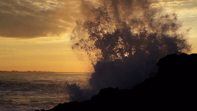 Wave hitting rocks at sunrise