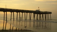Waves break beneath a wooden pier at the Jersey shore at Sunrise.  The sky is a golden orange.