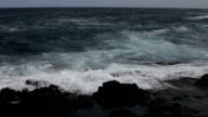 Waves Coming on shore against black lava