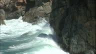 Waves crash against rocks on a California coast .
