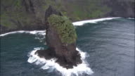 Waves crash into the base of a large island rock formation. Available in HD.