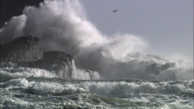 Waves crash over rocks during storm, New Zealand