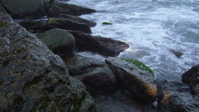 Waves crashing on shore rocks in slow motion