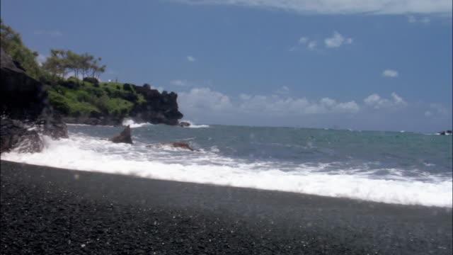 Waves hitting black rocks on beach in Maui, Hawaii