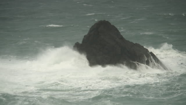 Waves hitting small rocky outcrop