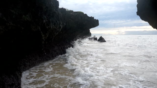 Waves hitting the rock formation on a sunrise