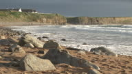 MS, Waves on rocky beach, surfers in distance, Clare County, Ireland