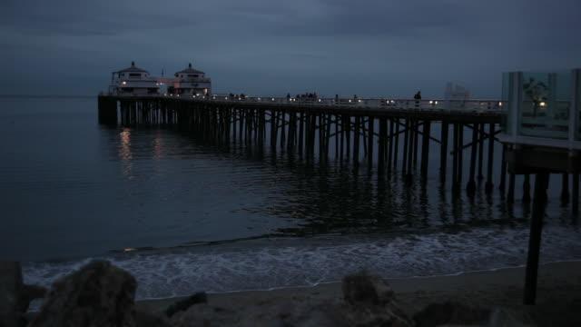 WS Waves roll in under a pier in Malibu / California