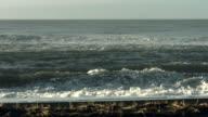 Waves roll onto a beach.