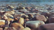 Waves roll over pebbles in sea