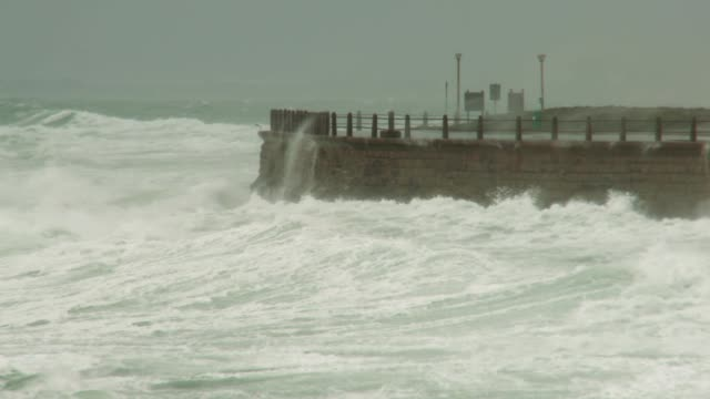 Waves violently break against the walls of Sea Point Beach. Available in HD.